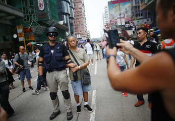 A man poses for a picture with a pro-democracy protester at a main street at Hong Kong's Mongkok shopping district