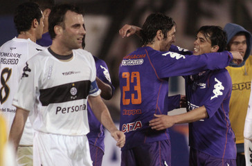 Argacha and Rodriguez of Uruguay's Defensor Sporting celebrate their progress to the next round beside Uglessich of Paraguay's Olimpia after their Copa Sudamericana soccer match in Asuncion