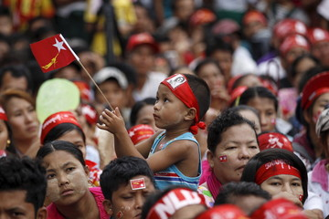 A boy holds a National League for Democracy (NLD) flag during a speech by Myanmar pro-democracy leader Aung San Suu Kyi as she campaigns in her constituency of Kawhmu township outside Yangon