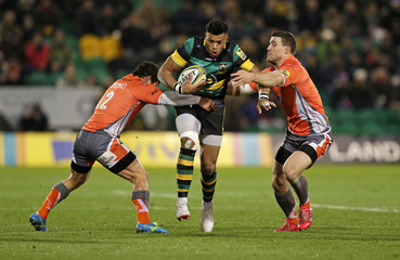 Luther Burrell of Northampton Saints tackled by Juan Pablo Socino (L) and Mark Wilson of Newcastle Falcons