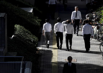 Businessmen walk in Tokyo's business district in Japan