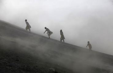 Pakistani Hindu devotees climb a mud volcano to perform a ritual offering of coconuts before visiting Shri Hinglaj Mata Temple located in Balochistan