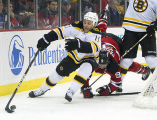 New Jersey Devils Zach Parise goes down following Boston Bruins Gregory Campbell in NHL game in Newark