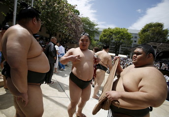 Sumo wrestlers wait for the start of the annual 'Honozumo' ceremonial sumo tournament dedicated to the Yasukuni Shrine in Tokyo, Japan