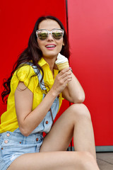 Beautiful  funny young hipster teen girl eating ice cream cone. laughs happy. Bright casual wear, denim shorts. Red background, urban style, sunglasses