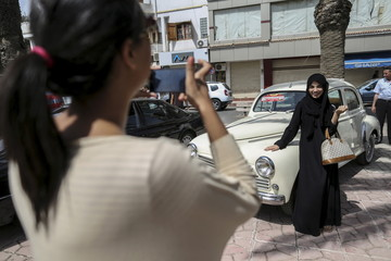 A woman photographs her friend during a vintage car exhibition in Rouiba, on the outskirt of Algiers