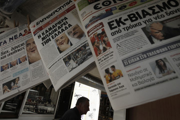 A man stands behind front pages of newspapers about IMF chief Strauss-Kahn's arrest at a central Athens kiosk