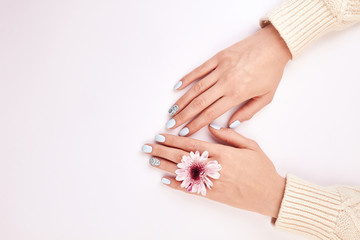 Fototapete - Female hands with a manicure and a pink flower.