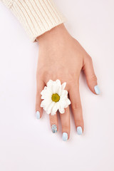 Fototapete - Beautiful female hand with a flower between the fingers.
