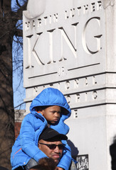 Walter Davis holds his four-year-old son Alexander Davis as they watch the King March in front of the the King Center to commemorate the holiday in Martin Luther King, Jr.'  honor in Atlanta