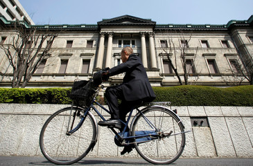 File picture of a man riding a bicycle past the BOJ building in Tokyo
