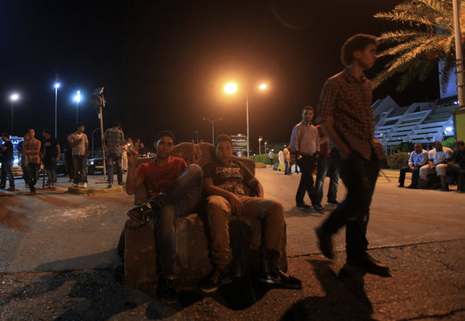 Men sit on a couch in the middle of a road leading to the city centre during a blockade by protesters in Benghazi