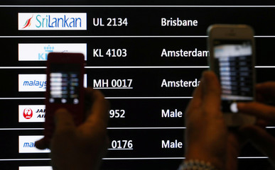 People take photos of a screen showing arrival details of Malaysia Airlines flight MH17 at Kuala Lumpur International Airport in Sepang