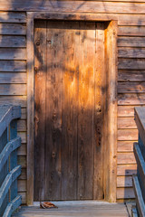 Front view of the wooden door of the old house with sunlight and shadows of trees on it