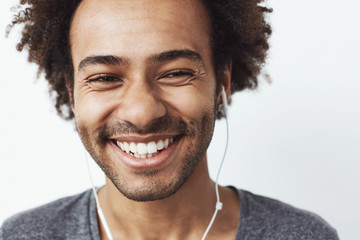 Close up of young happy african man smiling laughing over white background.