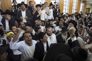 Ultra-Orthodox Jewish men recite prayers near the body of Rabbi Yosef before his funeral at a seminary in Jerusalem