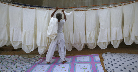 Saleem, a laundry man, lines up chair covers on a rope to dry along a street on the outskirts of Karachi