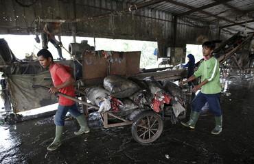 Workers transport sacks of plastic to recycle at a waste treatment facility at Bantar Gebang landfill in Bekasi
