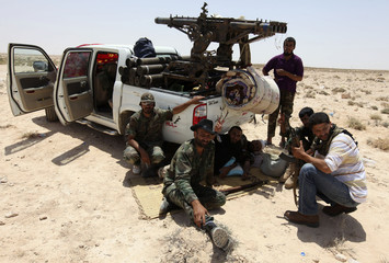 Libyan rebels are pictured near a vehicle as they make their way to the frontline, 40 km (25 miles) west of Ajdabiyah