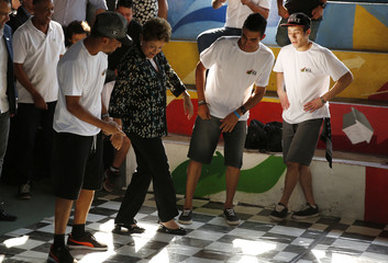 Hip hop dancers teach Brazil's President and Workers' Party presidential candidate Rousseff to dance during a campaign rally in Rio de Janeiro