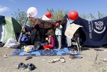 Migrant children rest in a tent on the side of a highway near Edirne