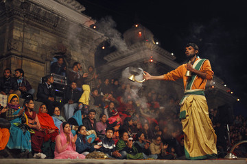 Priest offers an evening prayer as devotees sing holy songs on eve of Shivaratri festival at premises of Pashupatinath Temple in Kathmandu