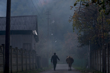 A Circassian villager walks past a cow at dusk in the village of Tkhagapsh in the Lazerevskoye district of Sochi