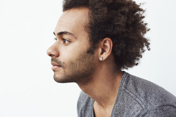 Portrait of young handsome african man in profile over white background.