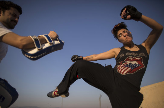 Interior designer Zahra Afridi kicks a punching bag during a kickboxing training session at her home in Islamabad
