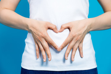 young woman who makes a heart shape by hands on her stomach.
