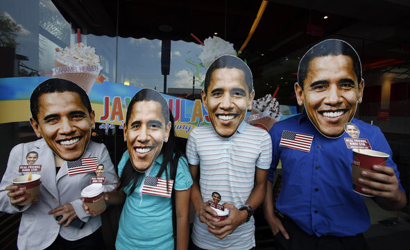 "Members of activist Party List group ""Akbayan"" don picture cut-out masks of U.S. President Barack Obama as they pose outside a coffee shop in Quezon city"