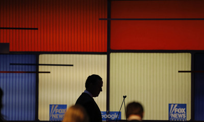 Republican U.S. presidential candidate and former U.S. Senator Rick Santorum is silhouetted against the debate backdrop during a commercial break