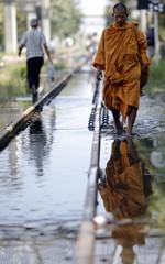 Buddhist monks walk along a flooded railway track in Bangkok