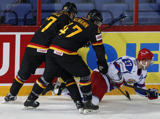 Germany's Gogulla and Ullmann fight for the puck with Russia's Tereshenko during their 2013 IIHF Ice Hockey World Championship preliminary round match at the Hartwall Arena in Helsinki