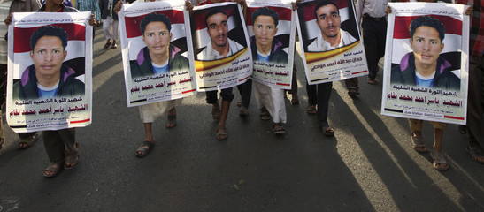 People carry the pictures of victims during a rally commemorating the second anniversary of a major clash between opposition protesters against former Yemeni president Ali Abdullah Saleh and security forces, in Sanaa