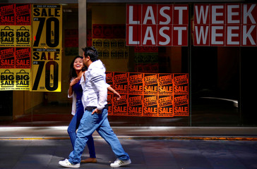 Pedestrians walk past the window of a retail store displaying sales posters along a main road in Sydney's CBD in Australia