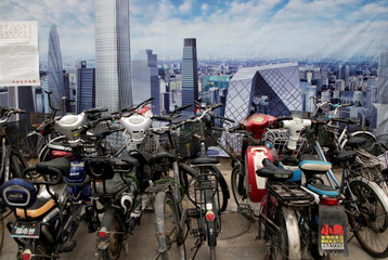 Bikes are parked in front of a poster bearing a picture of the CBD area in Beijing