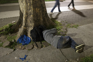 A migrant sleeps by a tree in a park near the main Belgrade's bus and train station