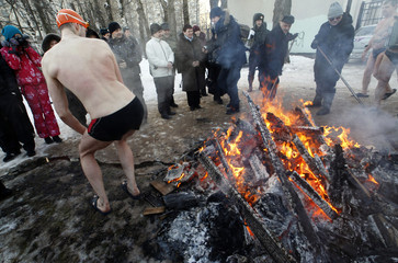 A winter swimmer warms himself near a fire after bathing in the icy waters of a pond at the Victory Park, with the air temperature at about minus 15 degrees Celsius in St. Petersburg
