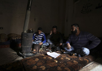 Free Syrian Army fighters warm themselves around a fire inside a room in Deir al-Zor