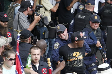 Police move in to contain protesters against the Ku Klux Klan during a rally at the statehouse in Columbia