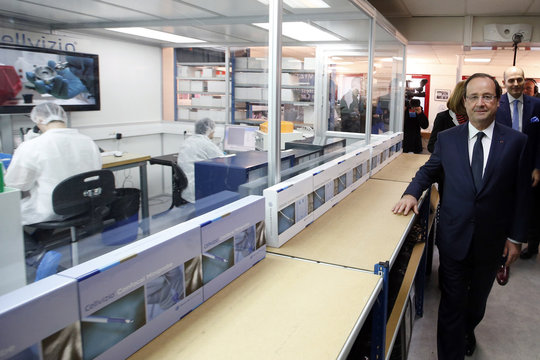 France's President Hollande walks ahead of Mauna Kea Technologies CEO Loiseau, during a visit of the presentation of Cellvizio, a Medical Endomicroscopy virtual assistant at Mauna Kea Technologies office in Paris