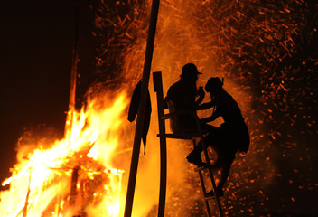 People climb a ladder to take pictures of the San Juan bonfire on the beach of Playa de Poniente in Gijon