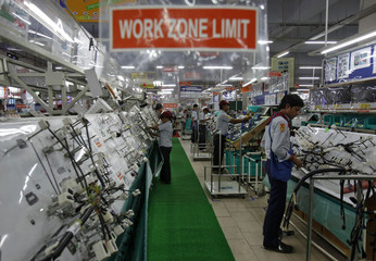 Employees work on a wiring for vehicles at the factory of the Samvardhana Motherson Group at Noida