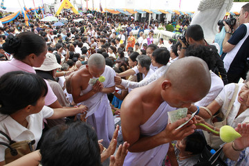 Thai hill tribesmen carry lotus flower buds as they arrive at the Wat Bechamabopit marble temple in Bangkok