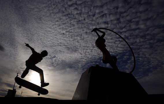 A young Brazilian boy practices his skateboarding skills near a sculpture at the beachfront of Fortaleza