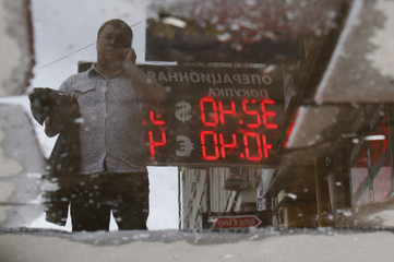 A sign with currency exchange rates is reflected in a puddle in Moscow