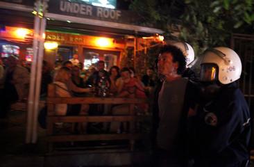 Riot policemen detain an anti-government protester along Kennedy street in central Ankara