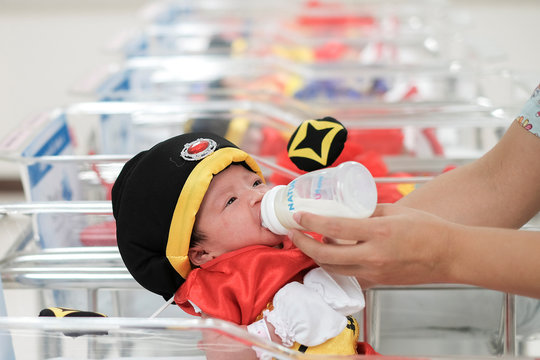 A nurse feeds a newborn baby wearing a chinese traditional costume to celebrate the Chinese New Year at the nursery room of Paolo Chockchai 4 Hospital, in Bangkok