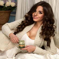 Beautiful girl drinking coffee in bed